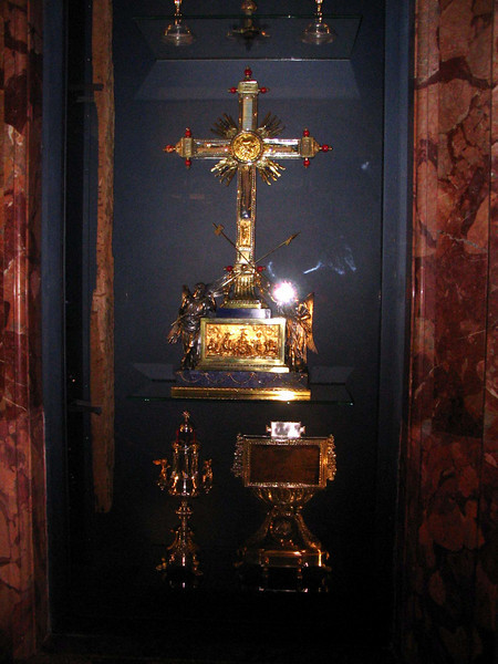 <center>Crucifixion Relics   <br><br>Rome, Italy<br><br>The crucifixion relics are housed in the Basilica of Santa Croce de Geruselem in Rome. This display case includes the incorruptable finger of St. Thomas, two thorns reputed to be from the Crown of Thorns, a nail from the crucifixion, wood from the True Cross, part of the crossbar from the good thief's cross, and the Titulus Crucis. This photograph does not include St. Thomas' finger or the thorns. I was only allowed one photograph and I need to ensure I had the Titulus in the photo. The large golden cross in the center contains the wood from the True Cross. The golden display at the bottom left has the nail and the block of wood on the right is the Titulus. Of all the relics in this case, only St. Thomas' finger and the Titulus are verifiably authentic, although there is at least one confirmed miracle associated with the wood of the Cross. (One young girl was cured of bone cancer after touching the wood.) All of the relics in this case were brought from Jeruselem by Helena Augusta, the mother of the emperor Constantine, in the 4th century AD. The Titulus and the wood from both crosses have been carbon dated to the early first century. </center>