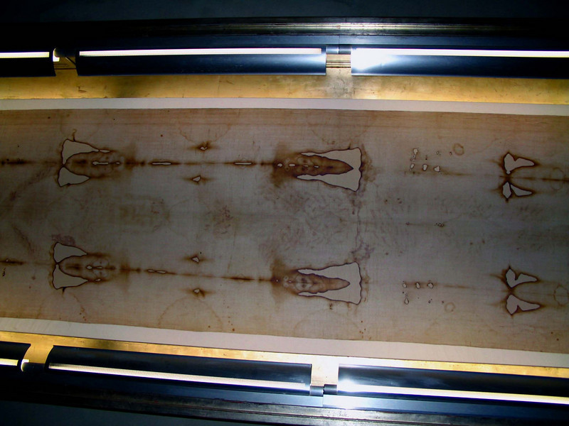 <center>Copy of the Shroud of Turin   <br><br>Rome, Italy<br><br>This is a photocopy of the Holy Shroud of Turin and is on display in the Basilica of Santa Croce de Geruselem. Even in Turin, only a copy is displayed except on special occassions, so this is about as close as you can get to the real shroud.  The Shroud of Turin is reputed to be the burial shroud of Jesus. The image on the shroud is consistent with the biblical account. Carbon dating, however, places the age of the shroud in the 14th century. That dating has been challenged, however, because the shroud was exposed to fire at that time and smoke from the fire invalidates carbon dating results. Pollen found on the shroud that came from Jeruselem and that had been extinct since the latter part of the first century lends a measure of authenticity to it. The image in the shroud also does not match the typical artistic renditions of Jesus in the 14th century, discrediting the idea that it could be a medieval forgery. </center>