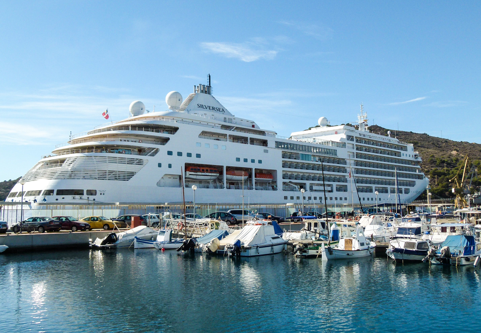 A luxury cruise ship docks next to small boats in Cartagena, Spain.