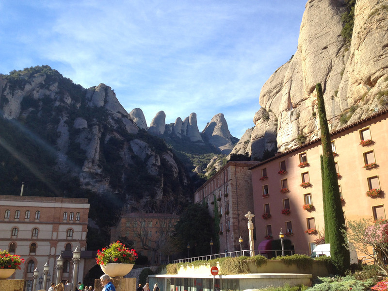 The pink walls of the benedictine monastery in Montserrat sit beneath stone capped mountains.