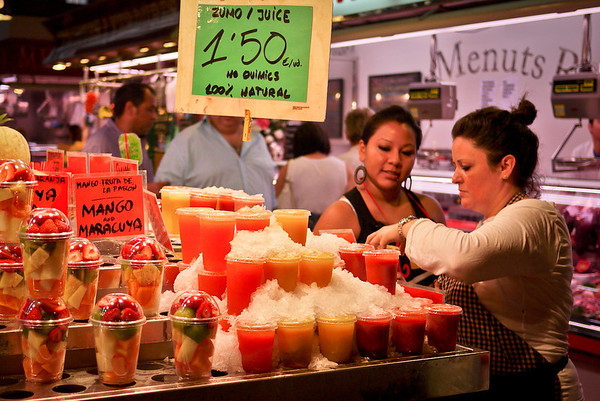 A vendor sells fresh juices in la Boqueria market in Barcelona, Spain.