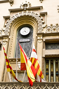 Spanish and Catalan flags wave from a building in Barcelona, Spain.