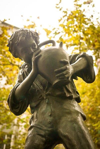 A statue of a boy drinking from a jug in Barcelona, Spain.