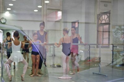 Young girls learn ballet as I look on through the glass on the streets of Barcelona, Spain.