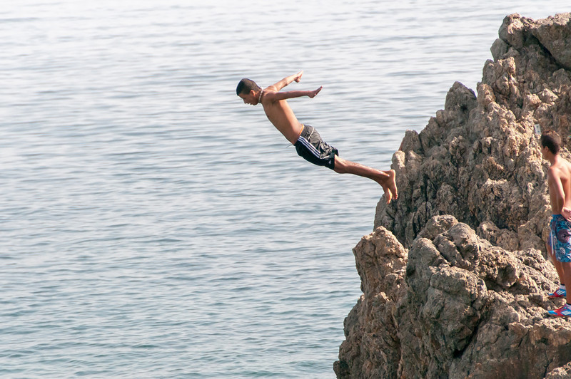 Diving off a rocky cliff in Ceuta, Spain