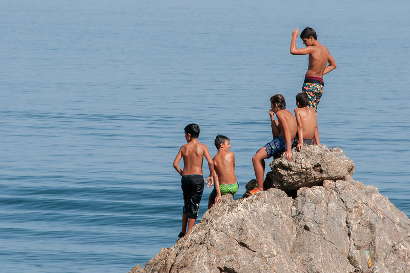 Boys getting ready to dive off a rocky cliff in Ceuta, Spain