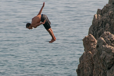 Diving into the ocean from a rocky cliff in Ceuta, Spain