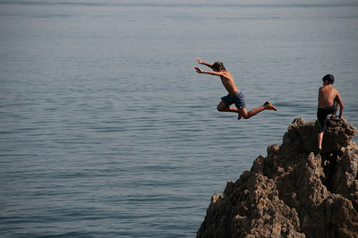 Jumping off a rocky cliff in Ceuta, Spain