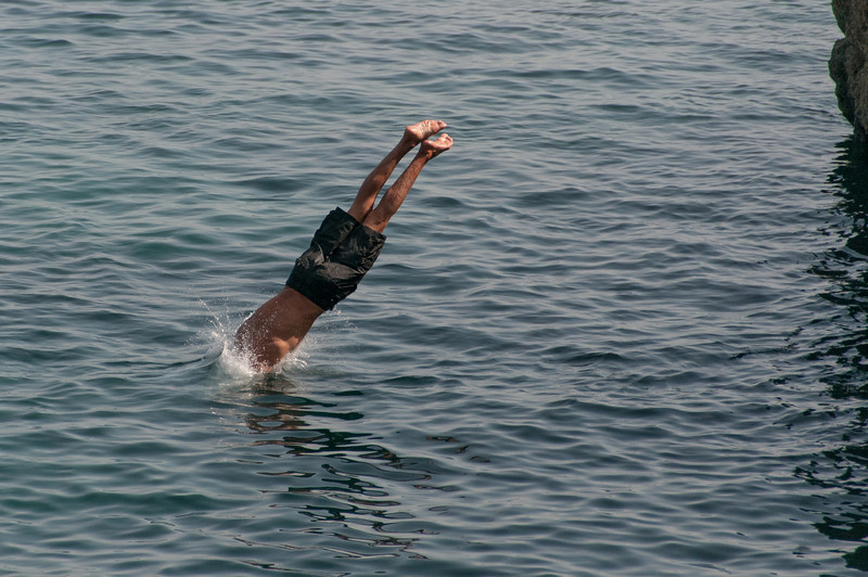 Man diving off a cliff in Ceuta, Spain