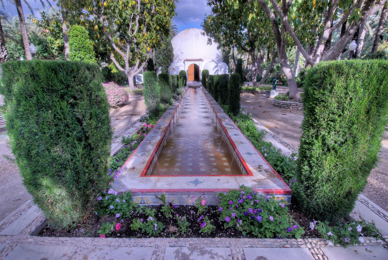 Long fountain in Palmeral of Elche in Spain