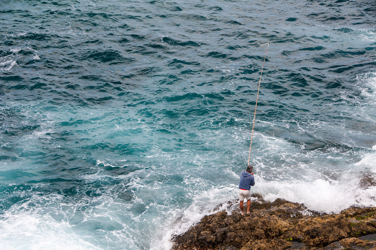 Man fishing on rocky coastline of Fuerteventura, Spain