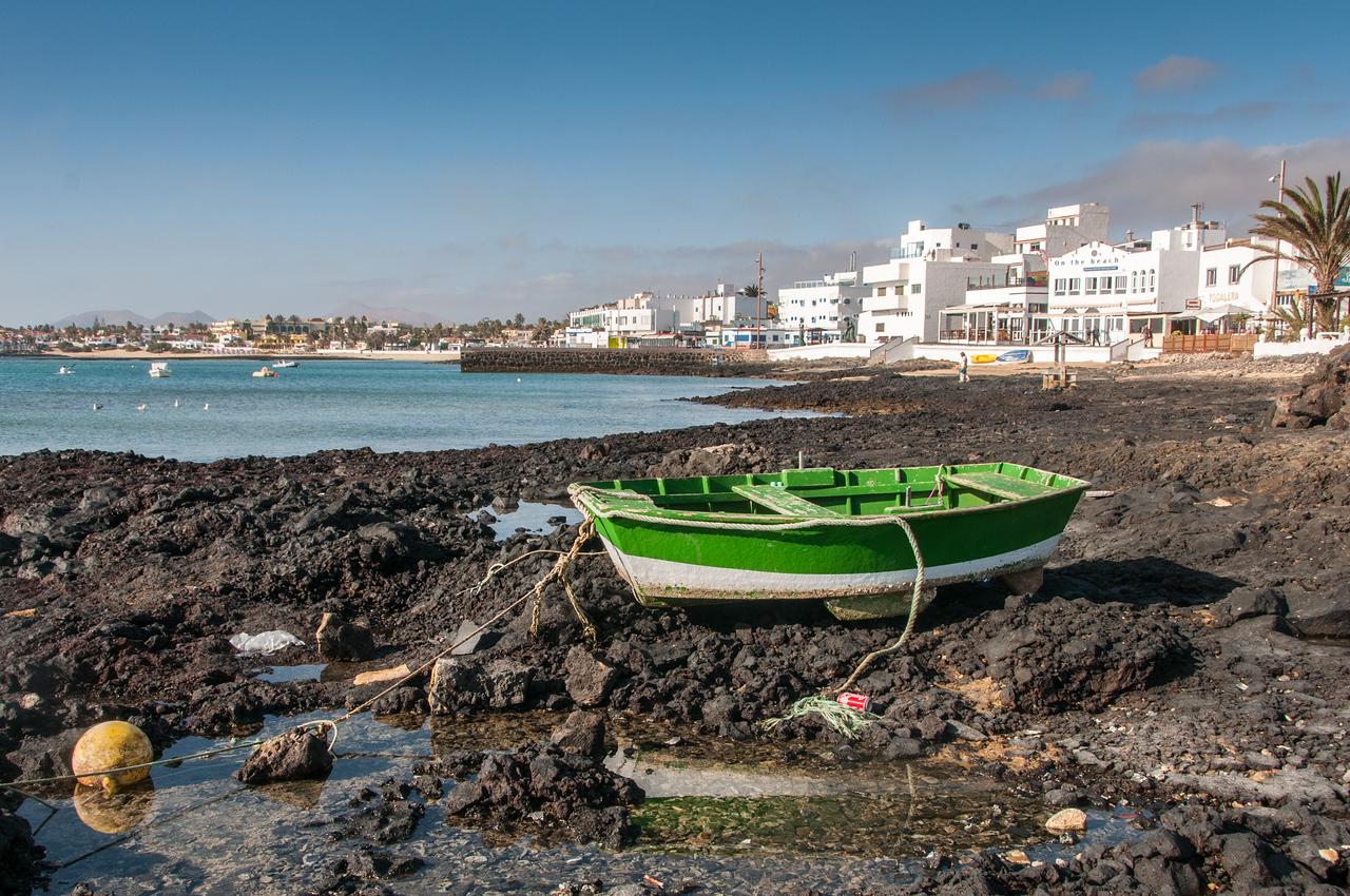 Solitary boat on a rocky beach in Corralejo, Fuerteventura, Spain