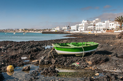 Solitary boat on a rocky beach in Corralejo, Fuerteventura, Spain