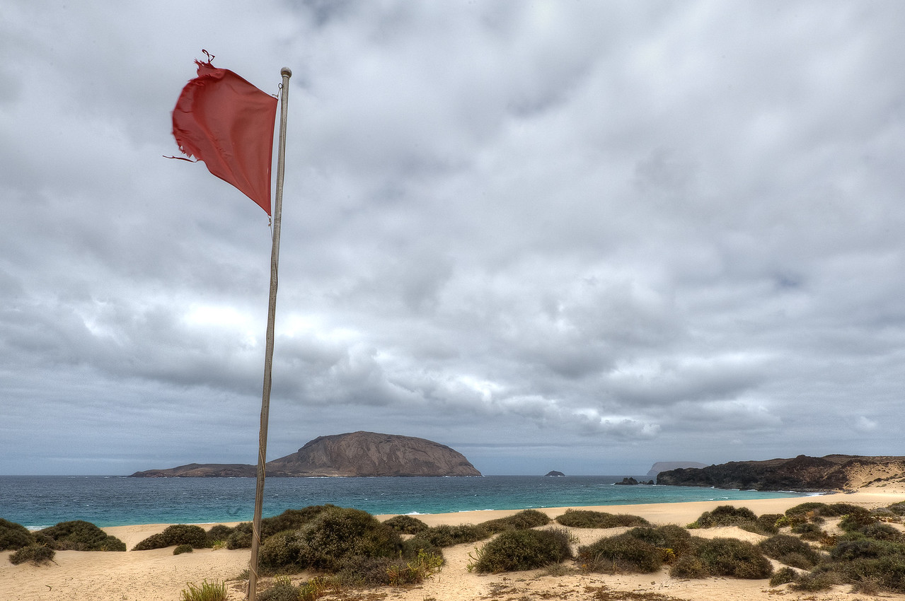 Red flag waving on the coastline of La Graciosa, Canary Islands, Spain