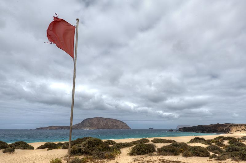 Red flag waving on the coastline of La Graciosa, Canary Islands, Spain
