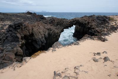 Small natural land bridge in the island of La Graciosa, Spain