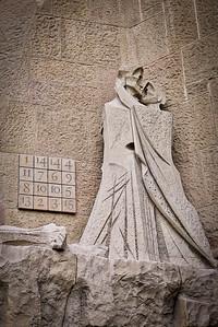 Guant figures embrace on the  Passion façade of La Sagrada Familia in Barcelona, Spain