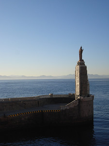 A statue of Jesus at the entrance of the port of Tarifa with a view of Morocco in the background,Tarifa - Spain.