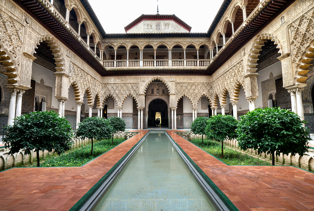 the central courtyard of the alcazar of seville with reflecting pool and detailed carved arches