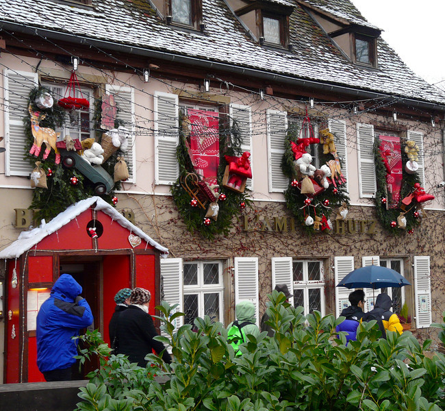 Stone house in Strasbourg with Christmas wreaths hanging over the windows.