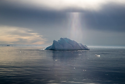 Another iceberg dramatically lit via a break in the clouds