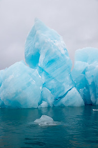 The dramatic blues of the glacial ice stand out against a grey sky
