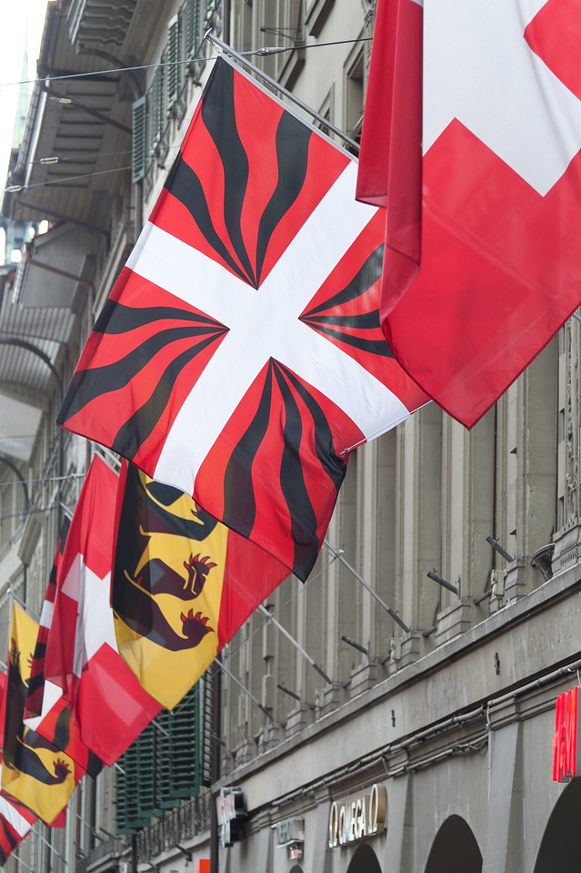 Flags raised along shopping promenades near Zytglogge clock tower in Bern, Switzerland