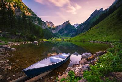Sunset over the Seealpsee lake with a boat in the Swiss Alps, Switzerland