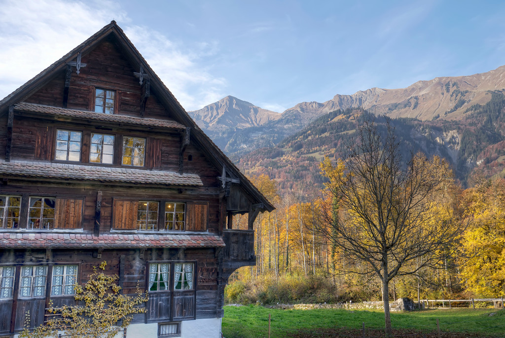 swiss lodge in autumn with mountains and blue sky in background