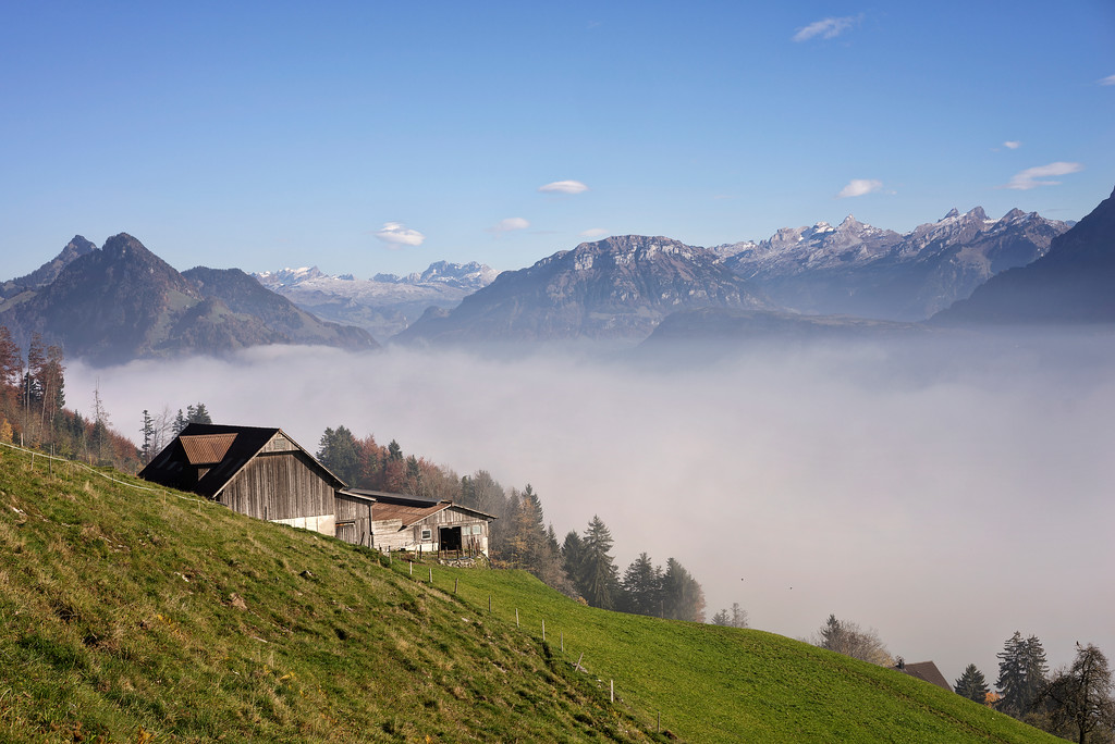 swiss alpine farmhouse with mountains and clouds and blue sky lucerne swtizerland