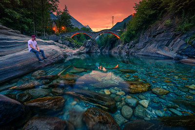 Tourist enjoys sunset at a river near stone bridge in Lavertezzo, Switzerland