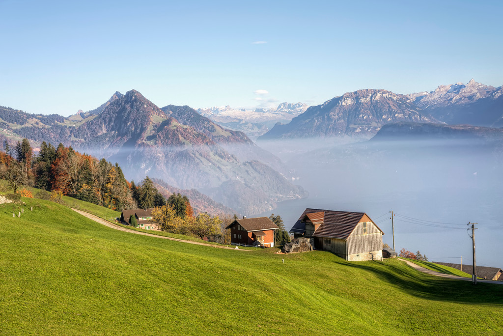 farmhouse on an alps hillside with view over mountains and lake lucerne in honneg switzerland