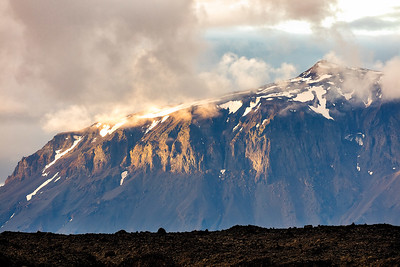 Mt Herd rises prominently above the lava field with a slash of sunlight breaking across it through the clouds