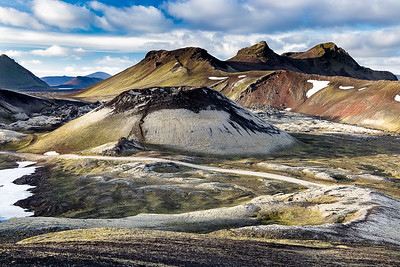 The highlands of Iceland offer a stark contrast of multicolored earth, black lava, white snow and green moss