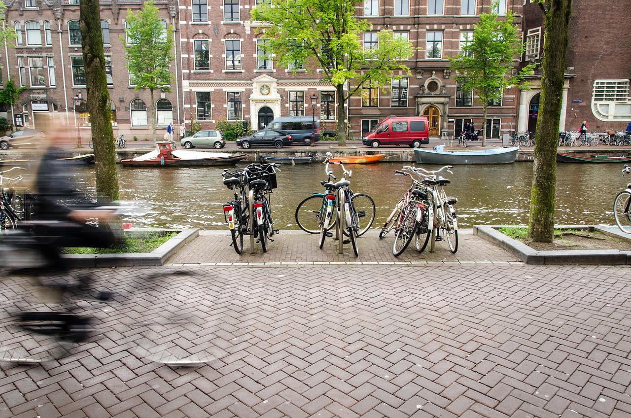 A bicyclist speeds along Kloveniersburgwal.