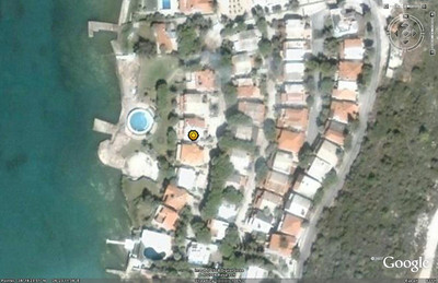 "The ""sun"" marks the beach house on this Google Earth image.  You can tell this image is several years old - due to an architectural dispute, half of the round pool and the jetty no longer exist."