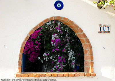 "A window in the wall of a house gives us a glimpse of the bougainville shrubs in the couryard.  The ""nazar boncuk"" (evil eye) is meant to ward off any bad luck that might befall the premises."