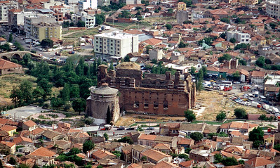 "The Temple of Serapis - also recognized as the ""Red Hall"" and the ""Red Basilica,"" is known locally as "" Kızıl Avlu"" (Red Courtyard).  The name is derived from the red bricks used in the construction of the temple.  This view of the Red Basilica is from the acropolis of Pergamum.  The Selinus River (Bergama Çayı - note bridge to the left) flows under the courtyard of Kızıl Avlu. It is believed that the river represented the Nile and thus, the water may have been used in rituals conducted here.  Photo posted by permission from:  www.HolyLandPhotos.org"