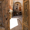 A glimpse through the heavily-carved door of the vocational school reveals a beautiful courtyard.