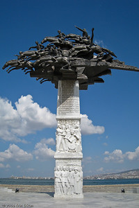 """Kordon - This monument in Gündoğdu Square is known locally as """"Cumhuriyet Ağacı Anıtı"""" (Republic Tree Monument).  It was erected to commemorate the 80th anniversary of Turkey becoming a republic.  The top portion represents Atatürk and the Turkish cavalry fighting the War of Independence.  The reliefs carved on the marble base depict scenes associated with Turkey becoming a republic."""