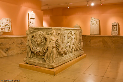 """Sarcaphogus - Roman Period (Smyrna [İzmir]) History & Art Museum - Kültür Park  Sarcaphogus (meaning """"flesh-eater"""" in Greek) is a coffin for inhumation burials, widely used throughout the Roman Empire starting in the 2nd Century AD. The most luxurious were of marble, but they were also made of other stones, lead, and wood.  The most common shape for Roman sarcophagi is a low rectangular box and a flat lid.  The carved garlands evoke the actual garlands that were used to decorate tombs and altars."""