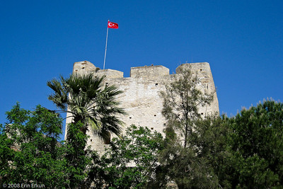 The Turkish flag proudly flaps in the wind from one of the towers of the Fortress of Çeşme.