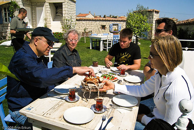 "Alaçat Kırevi - Breakfast is served!  The tea has been poured, the cucumbers and tomatoes drizzled with delicious olive oil placed on the table, and the ""gevrek"" is being divied up.  (Gevrek, also known as ""simit,"" is a circular bread covered in sesame seeds.  The word literally means ""crisp"" - very appropriate to this particular Turkish delicacy.)"