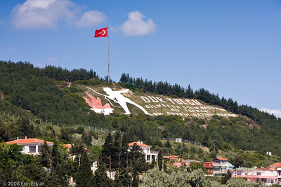 "The quote on the hill is taken from ""Bir Yolcuya"" (To a Wayfarer), a poem by Necmettin Halil Onan.  These words are translated as: ""Halt, wayfarer; this land that you step on without thought is where an era came to an end."""