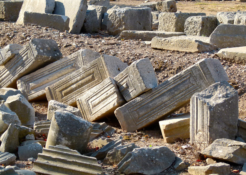 Roman columns rest against each other on the ground at Ephesus.