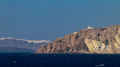 Akrotiri Lighthouse on cliff with Fira in background