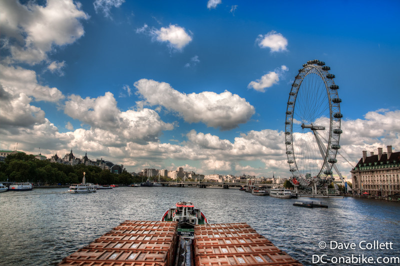 Rubbish boat going under the bridge, with the London Eye