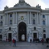 A panoramic picture of Hofburg Palace standing in the center of Michaelerplatz, looking through to the courtyard.