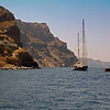 Sailboats anchored in a bay in the caldera of Santorini, Greece.