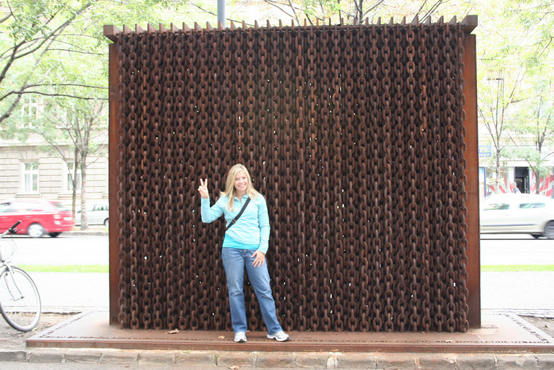 Cathy displaying the peace sign in front of a symbolic iron curtain.....Can't we all just get along?